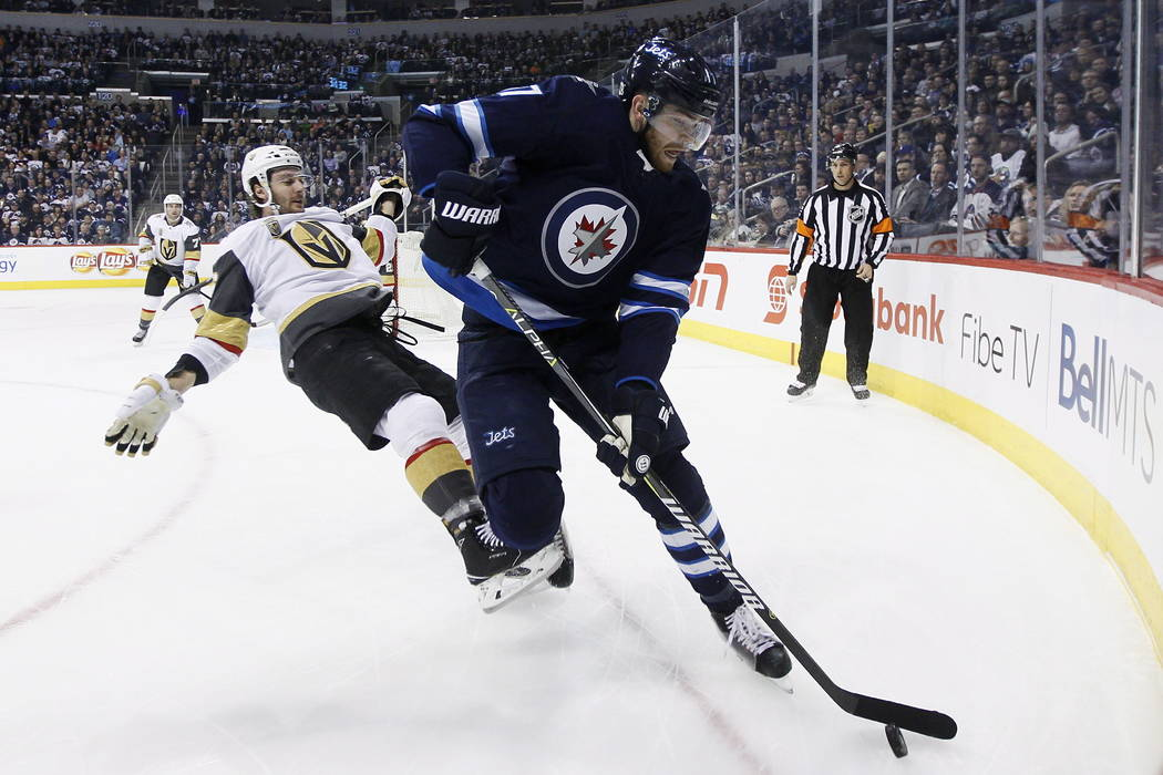 Vegas Golden Knights' Colin Miller (6) loses the fight for the puck against Winnipeg Jets' Adam Lowry (17) during the second period of an NHL hockey game Thursday, Feb. 1, 2018, in Winnipeg, Manit ...
