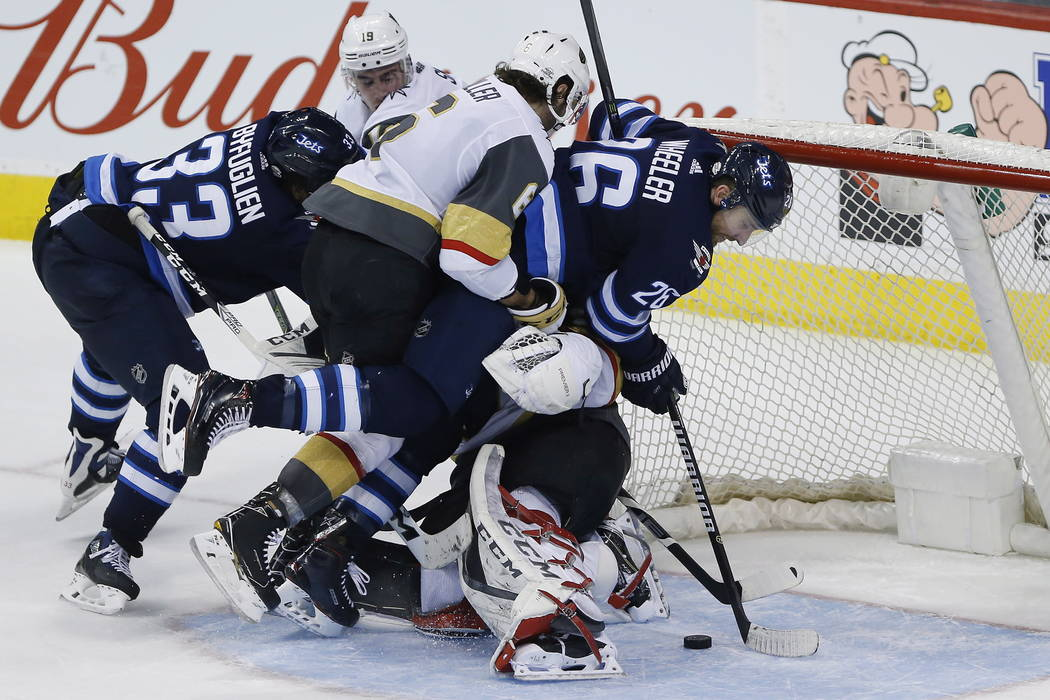 Winnipeg Jets' Blake Wheeler (26) can't get his stick on the puck as he and Vegas Golden Knights' Colin Miller (6) crash into Knights goaltender Marc-Andre Fleury during overtime in an NHL hockey  ...
