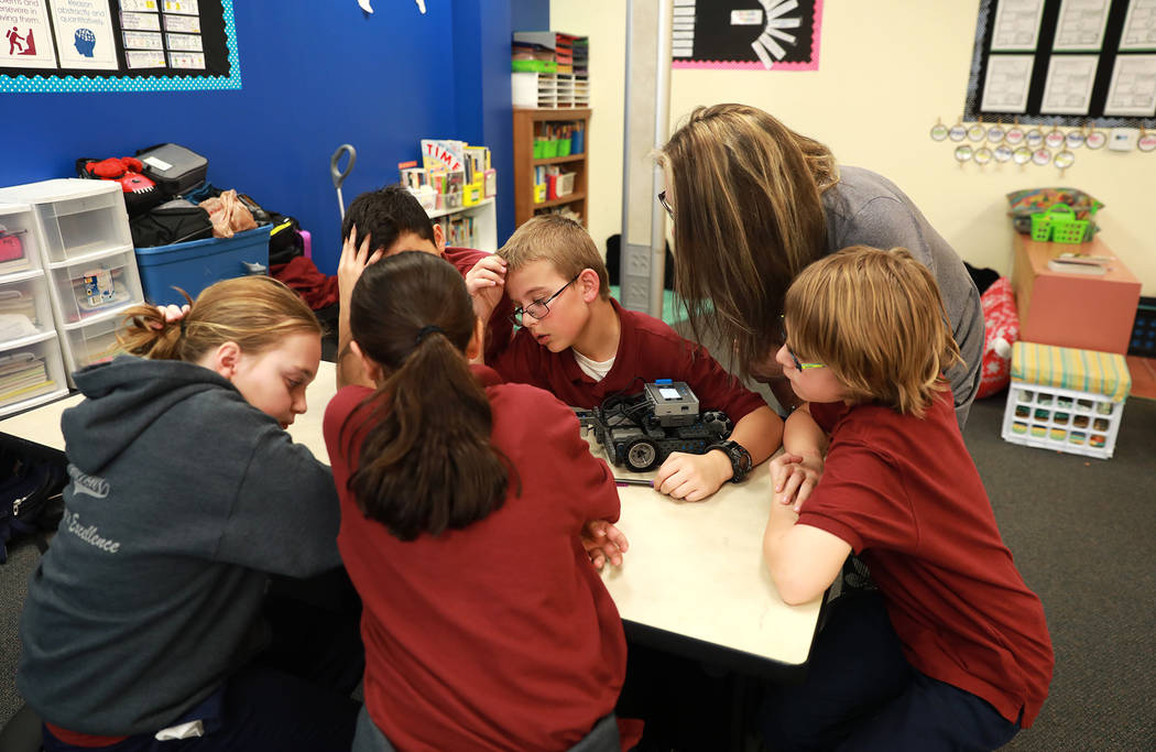 Teacher Nancy Bleuer talks to a group of students while they work on their robot as part of Project Lead the Way, a science, technology, engineering, arts and math program that combines the Next G ...