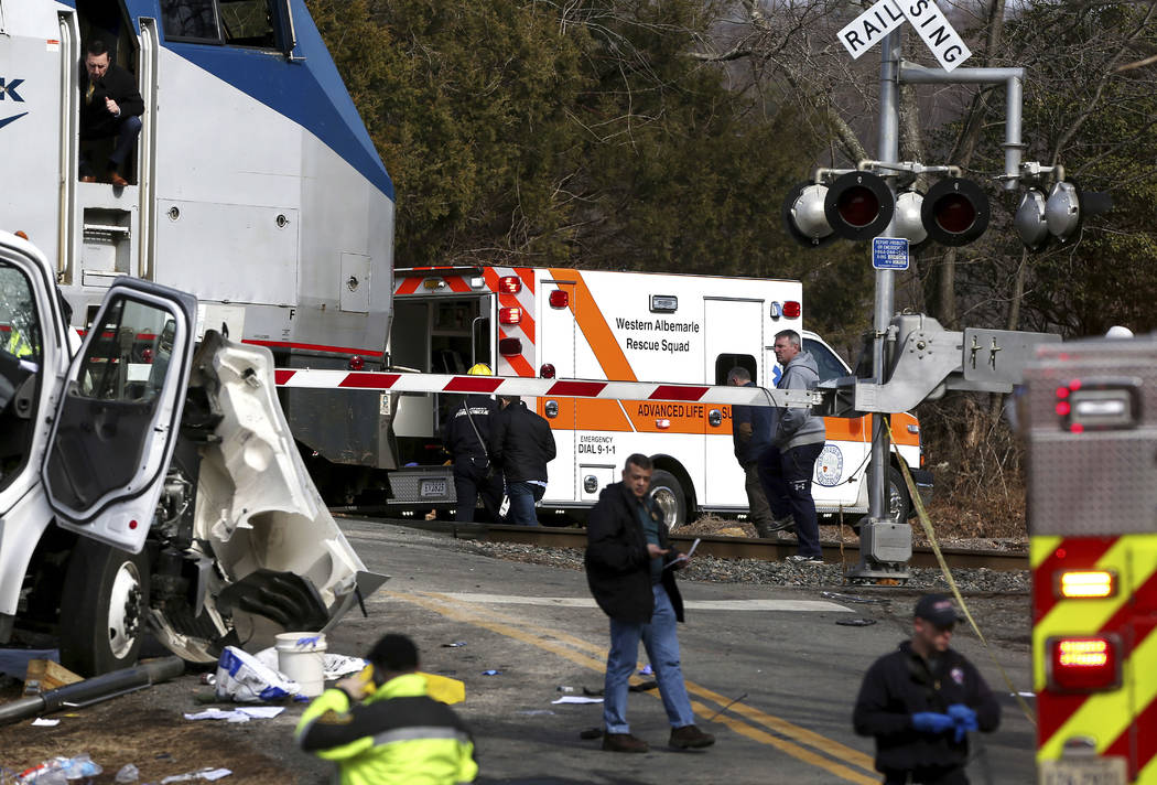 The railroad crossing arm is seen lowered next to the scene of where an Amtrak train carrying multiple Republican lawmakers crashed into a garbage truck  in Crozet, Va., on Wednesday, Jan. 31, 201 ...