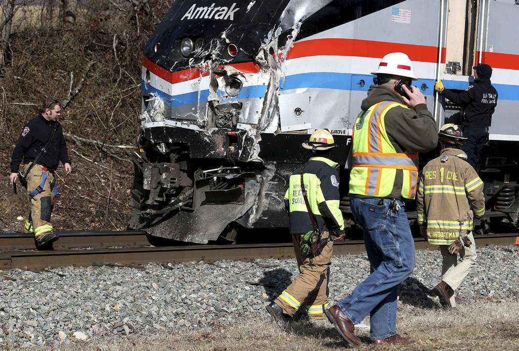 Emergency personnel inspect the lead engine of an Amtrak train that was carrying multiple Republican lawmakers that crashed into a garbage truck  in Crozet, Va., on Wednesday, Jan. 31, 2018.  A ch ...