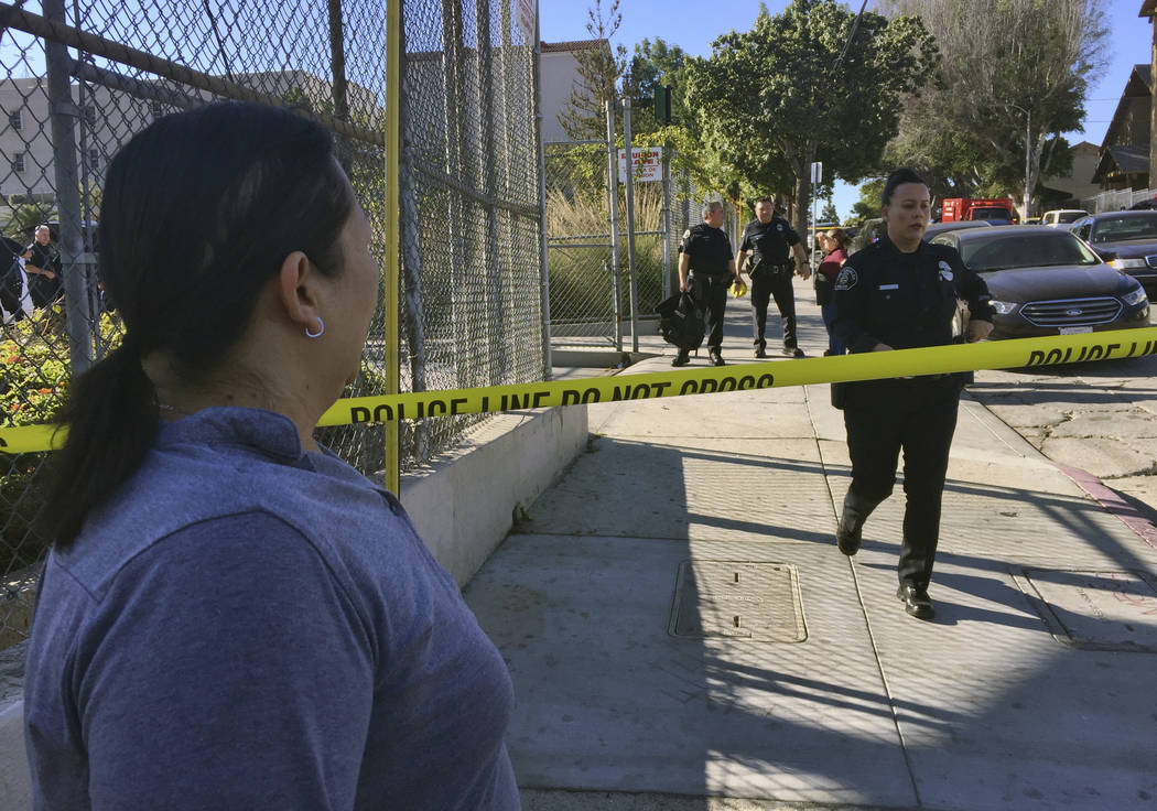 Gloria Echeverria watches as Los Angeles police officers close off a street where a shooting occurred at a Salvador B. Castro Middle School in Los Angeles on Thursday, Feb. 1, 2018. Two students w ...