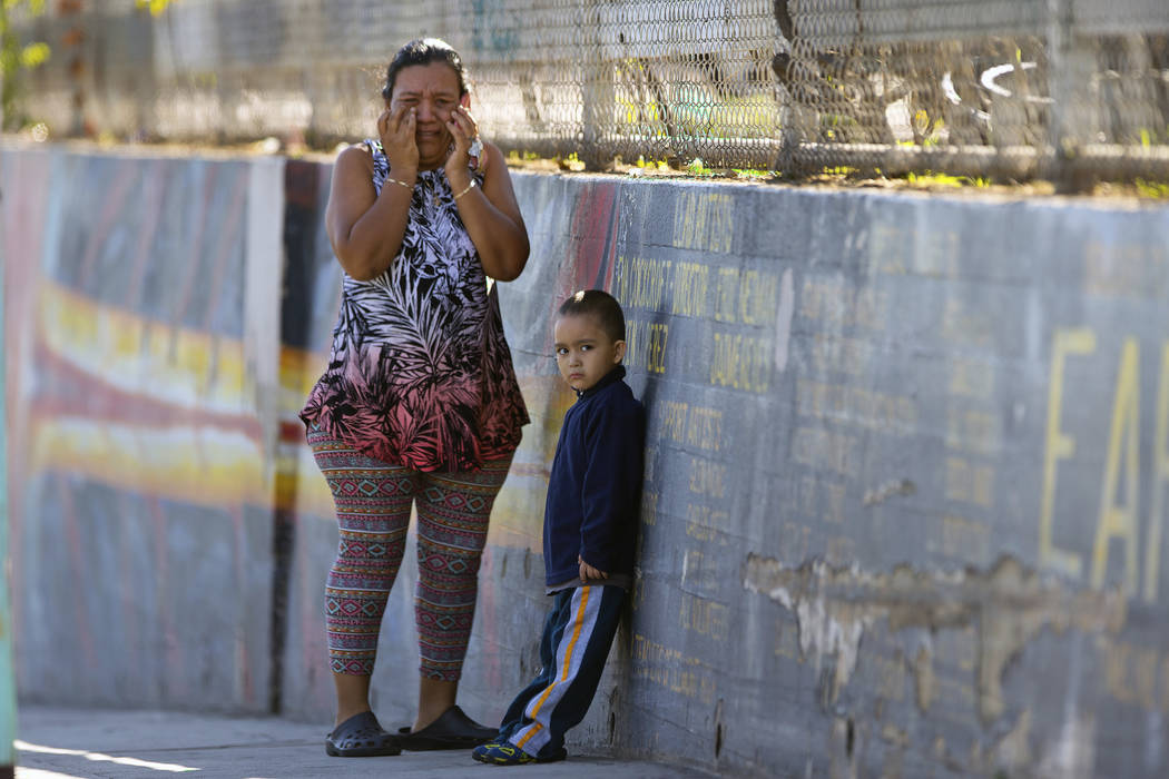 Elizabeth Acevedo and her son Andres, 3, wait for news of her son Jose, an eighth-grader at Salvador B. Castro Middle School in Los Angeles Thursday, Feb. 1, 2018. Two students were shot and wound ...