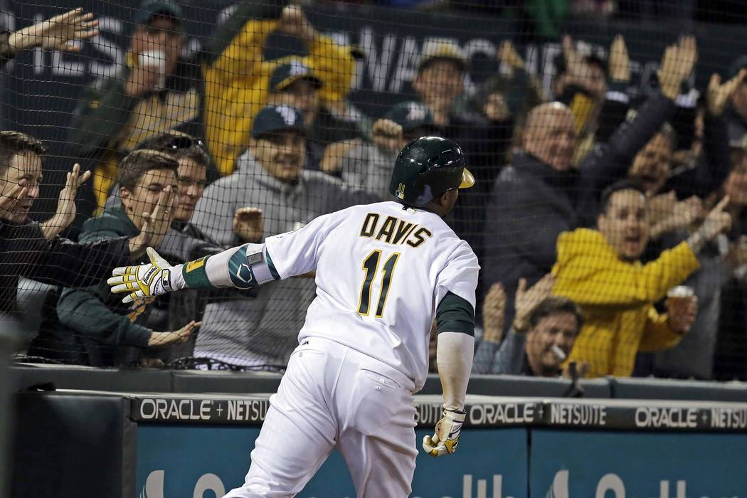 Oakland Athletics' Rajai Davis celebrates with fans as he scores on a throwing error after hitting a two-run triple in Oakland, Calif., April 4, 2017. All 30 major league ballparks will have expan ...