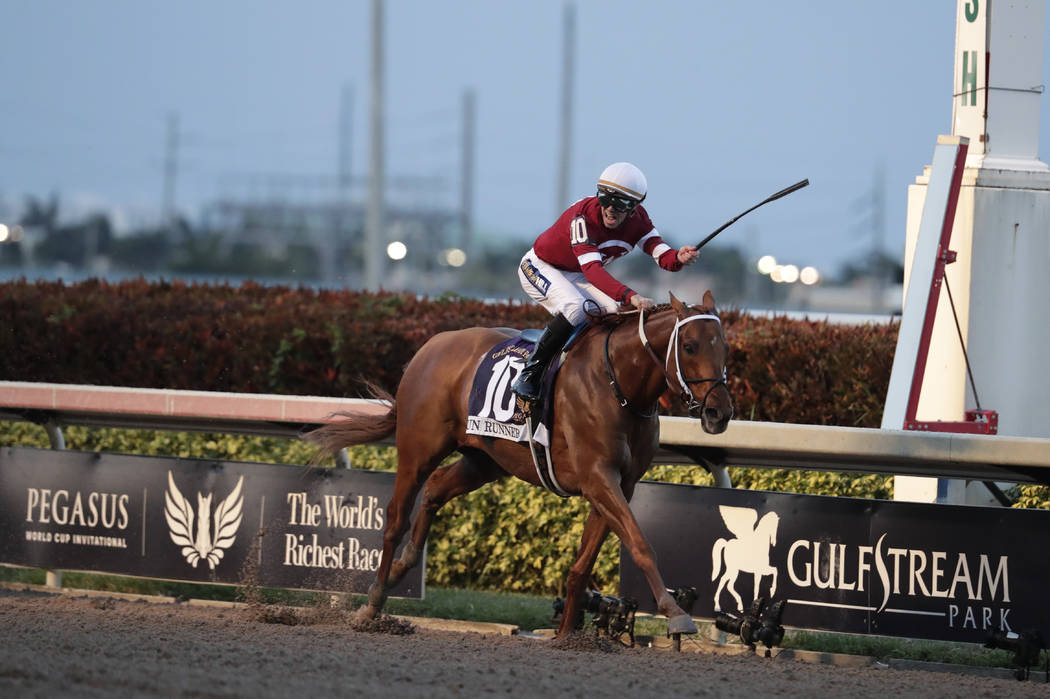 Jockey Florent Geroux approaches the finish line riding Gun Runner to win the Pegasus World Cup Invitational horse race, Saturday, Jan. 27, 2018, at Gulfstream Park in Hallandale Beach, Fla. (AP P ...