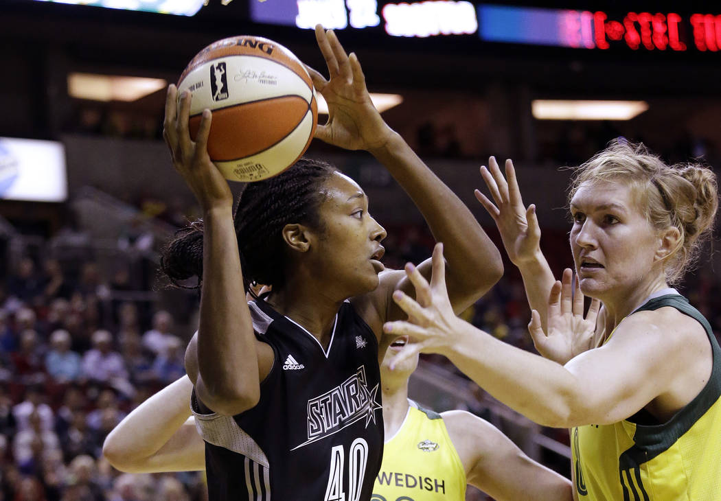 San Antonio Stars' Kayla Alexander (40) looks for room to pass as Seattle Storm's Sami Whitcomb defends in the first half of a WNBA basketball game Sunday, June 18, 2017, in Seattle. (AP Photo/Ela ...