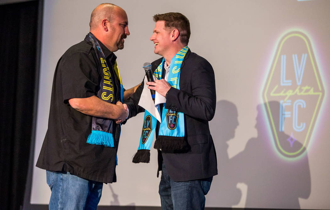 Las Vegas Lights FC soccer team owner Brett Lashbrook, right, shakes hands with Loren Becker, Zappos Experience and Community Team Manager, during a jersey reveal event at the Zappos Downtown camp ...