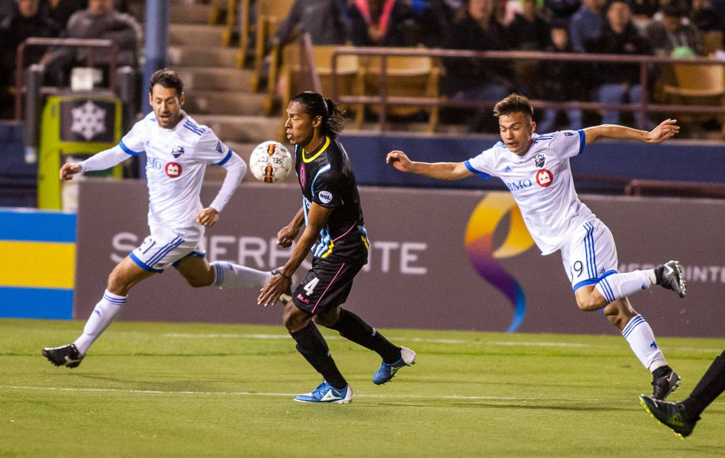 Las Vegas Lights' Joel Huiqui chests the ball while being chased by Montreal Impact players Matteo Mancosu, left, and Ken Krolicki, right, during the first Las Vegas Lights FC game at Cashman Fiel ...