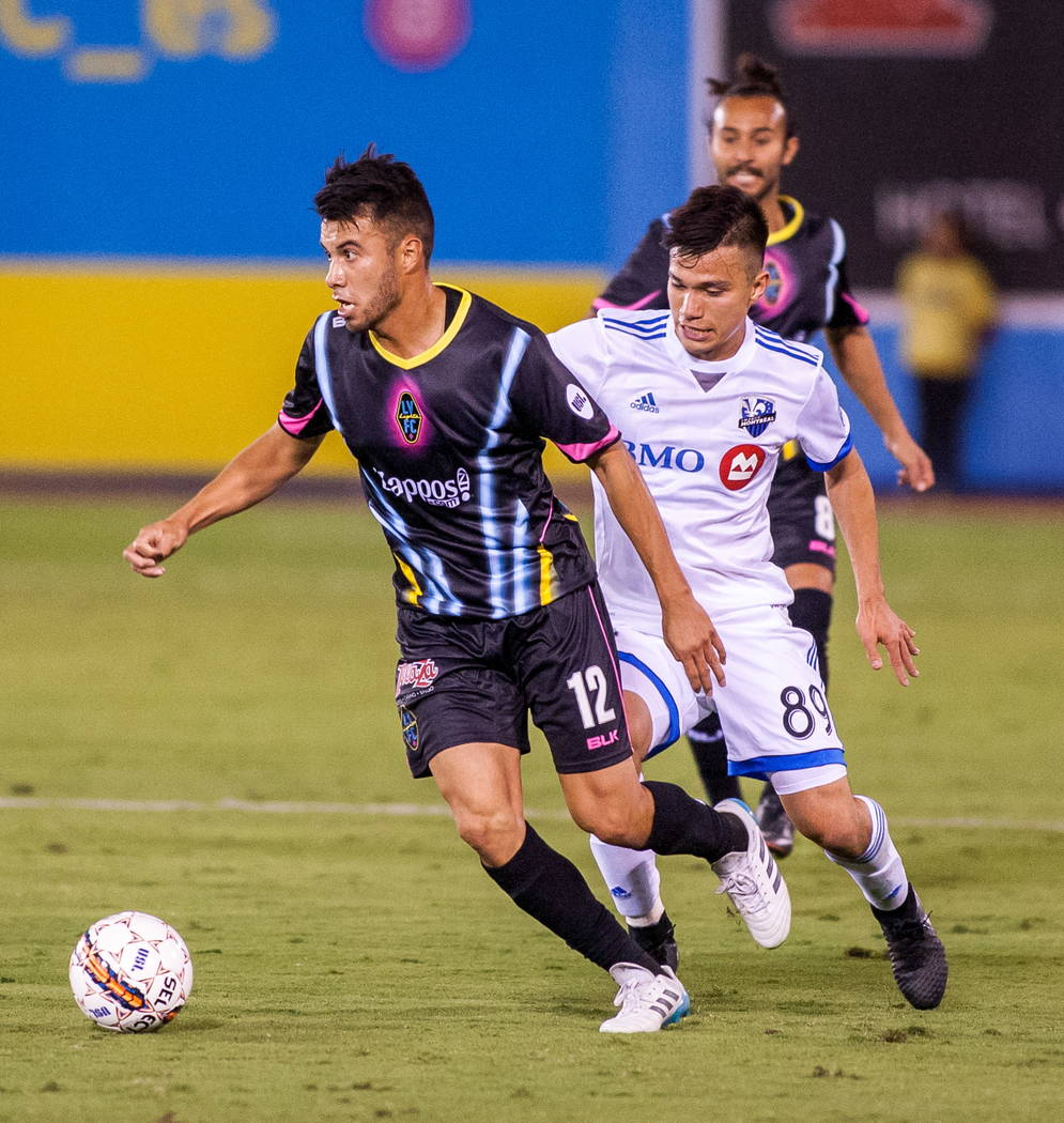 Las Vegas Lights' Carlos Alvarez tries to keep ahead of Montreal's Ken Krolicki during the first Las Vegas Lights FC game at Cashman Field in Las Vegas on Saturday, Feb. 10, 2018.  Patrick Connoll ...