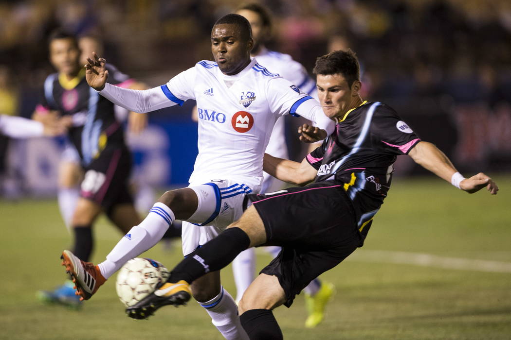 Las Vegas Lights FC Marcelo Thomas Matt (21) kicks the ball with pressure from Montreal Impact's Chris Duvall (18)  during the exhibition match at Cashman Field in Las Vegas, Saturday, Feb. ...