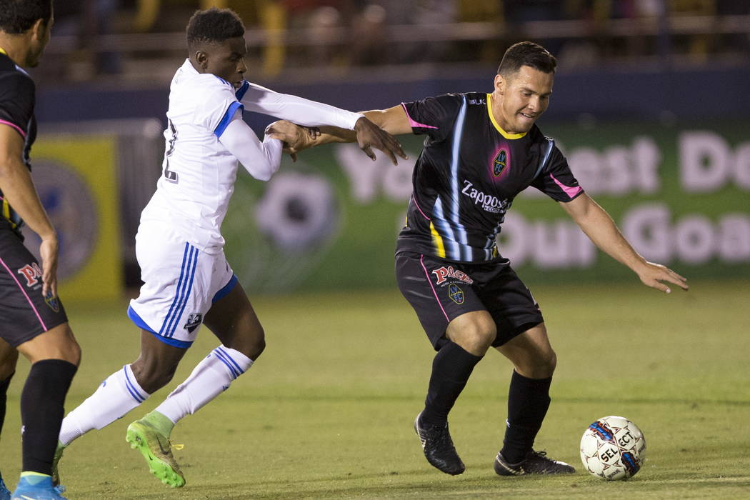 Montreal Impact's Cle´ment Bayiha (92) fights for the ball against and Las Vegas Lights FC Marcelo Julian Portugal (26) during the exhibition match at Cashman Field in Las Vegas, Saturday, Fe ...
