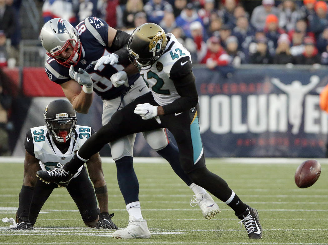 New England Patriots tight end Rob Gronkowski (87) is hit by Jacksonville Jaguars safety Barry Church (42) as he breaks up a pass during the first half of the AFC championship NFL football game, S ...