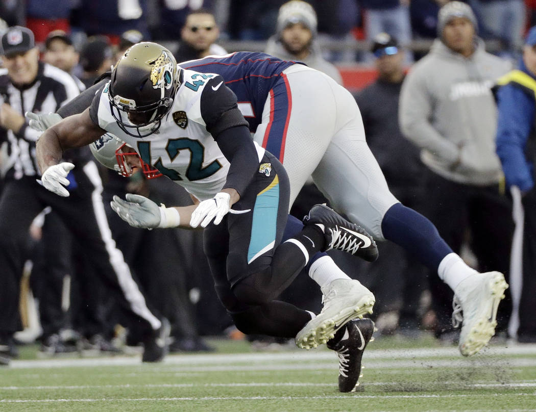 New England Patriots tight end Rob Gronkowski, rear, is hit by Jacksonville Jaguars safety Barry Church (42) as he breaks up a pass during the first half of the AFC championship NFL football game, ...