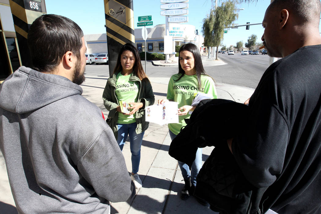 Kristel Roxas, second from left, and Valarie Goff hand out flier with photos of missing children to Irvin Romero, left, and Robert Scott on East Sahara during The Big Search campaign Friday, Feb.  ...