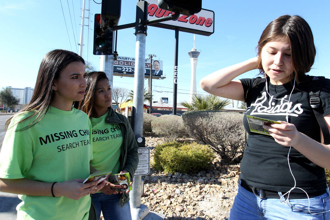 Valarie Goff, left, and Kristel Roxas, hand out flyers with photos of missing children to Vanessa Farfan on East Sahara during The Big Search campaign Friday, Feb. 2, 2018. Farfan said she recogni ...