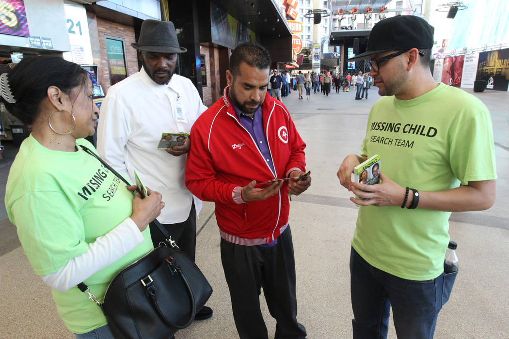 Wanda Ramsey, left, and Roberto Garcia, right, hand out flyers with photos of missing children to Timothy Edward, second from left, and Hector Montes at the Fremont Street Experience during The Bi ...