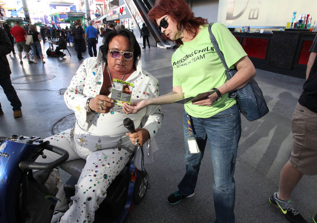 Annette Adams, right, hands out flyers with photos of missing to Michael Romeo at the Fremont Street Experience during The Big Search campaign Friday, Feb. 2, 2018. Volunteers distributed the flye ...