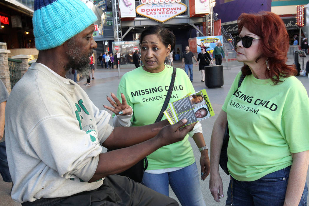 Annette Adams, right, and Wanda Ramsey hand out flyers with photos of missing to Calvin Wilson at the Fremont Street Experience during The Big Search campaign Friday, Feb. 2, 2018. Volunteers dist ...