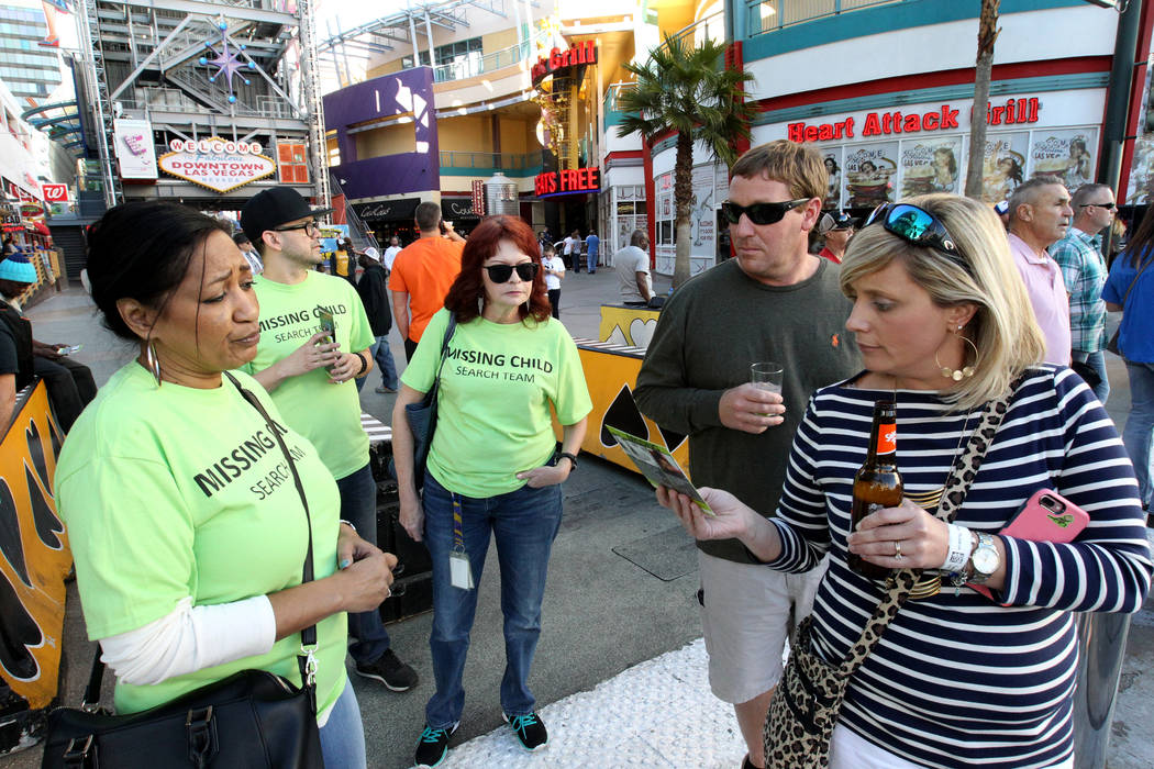 Wanda Ramsey, from left, Roberto Garcia and Annette Adams hand out flyers with photos of missing children to a couple who declined to give their names on East Fremont Street during The Big Search  ...
