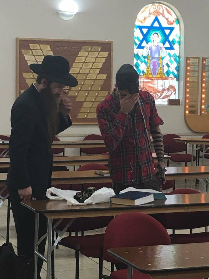 Shimon Abta wraps tefillin, Jewish prayer boxes, with his rabbi in Las Vegas on Jan. 8, 2017. Courtesy of Esther Abta.