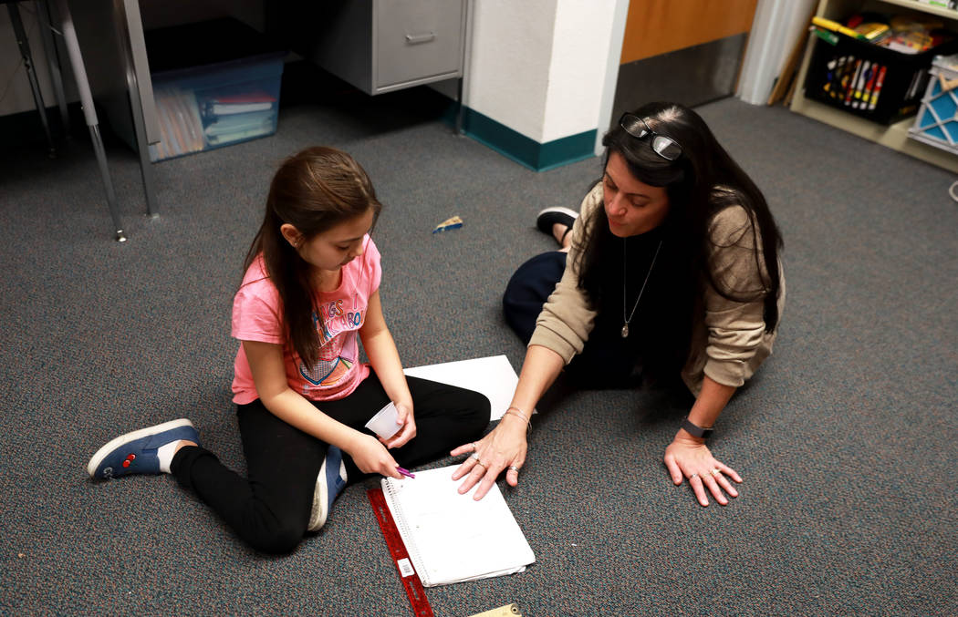 Principal Tammy Villarreal-Crabb helps Adrianna Figueroa, 9, with her class assignment at Doris French Elementary School, which went from being ranked two stars to five stars, in Las Vegas, Friday ...