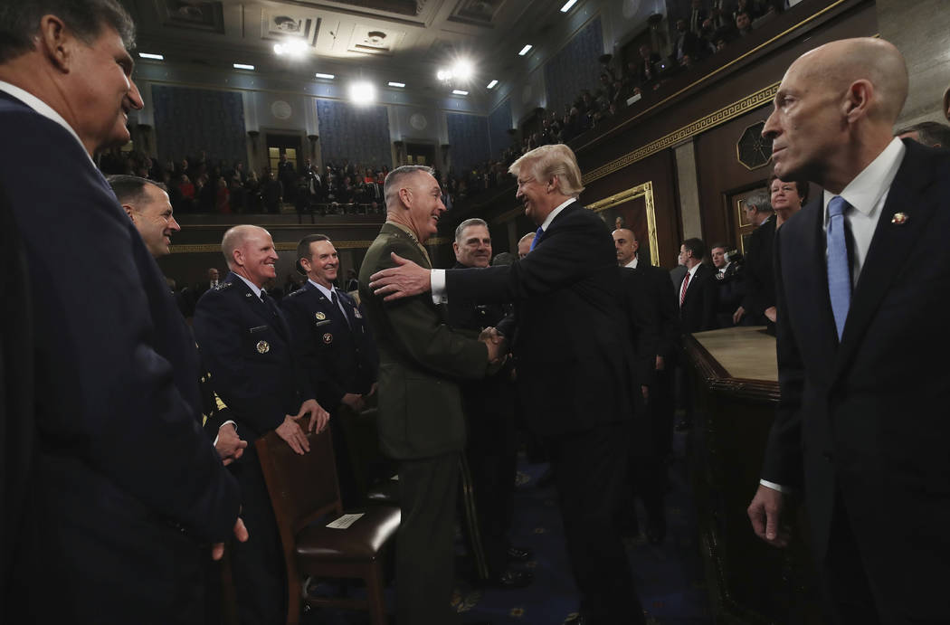 President Donald Trump greets Chairman of the Joint Chiefs of Staff Gen. Joseph Dunford after delivering his first State of the Union address in the House chamber of the U.S. Capitol to a joint se ...