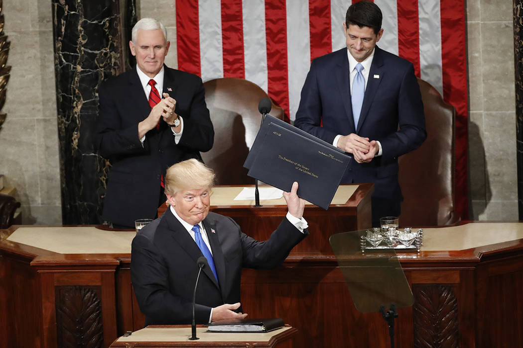 President Donald Trump holds up copies of his speech before the State of the Union address to a joint session of Congress on Capitol Hill in Washington, Tuesday, Jan. 30, 2018. (AP Photo/Pablo Mar ...