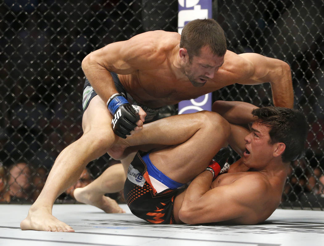 Luke Rockhold, top, fights against Lyoto Machida during a UFC mixed martial arts bout, Saturday, April 18, 2015, in Newark, N.J. (AP Photo/Julio Cortez)