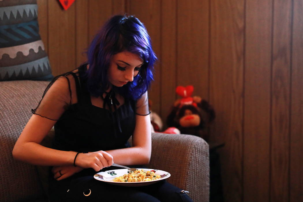 Faith Hubbard clutches her stomach to apply pressure while she eats at her home in Winterwood Village in Las Vegas on Tuesday, Feb. 6, 2018. After surviving the car accident two years ago, Hubbard ...