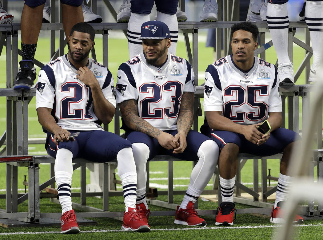 New England Patriots cornerback Malcolm Butler (21), strong safety Patrick Chung (23), and cornerback Eric Rowe (25) wait for their team photo to be made in U.S. Bank Stadium Saturday, Feb. 3, 201 ...