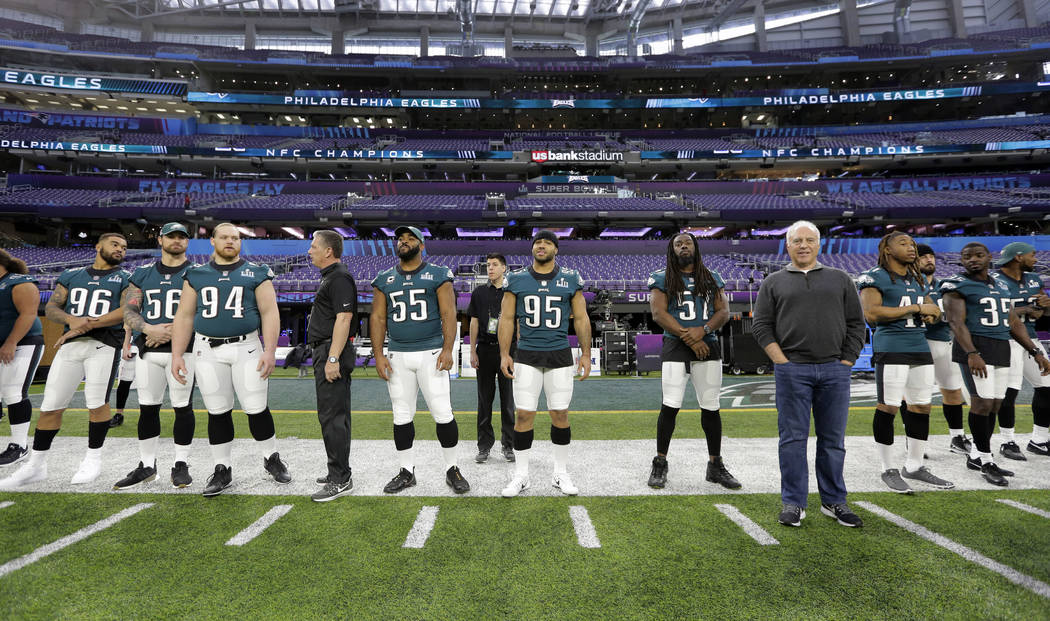 Philadelphia Eagles owner Jeffrey Lurie, front right, stands with players as they prepare for a walk through for the NFL Super Bowl 52 football game at U.S. Bank Stadium, Saturday, Feb. 3, 2018, i ...
