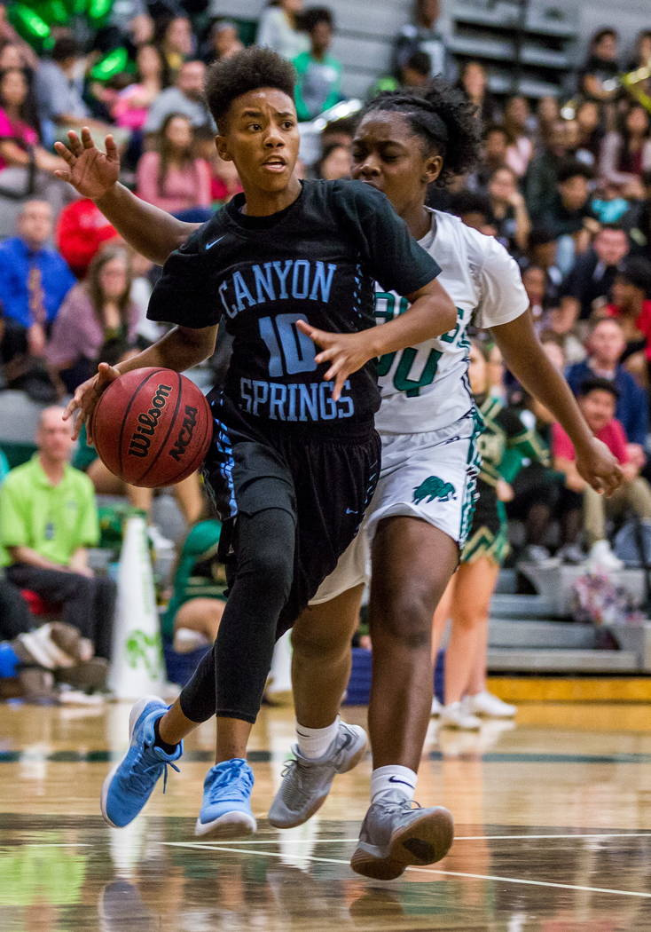 Canyon Springs' Kayla Johnson (10) dribbles around Rancho's Kyndal Ricks (24) at Rancho High School in Las Vegas on Tuesday, Feb. 6, 2018. Canyon Springs won 58-38.  Patrick Connolly Las Vegas Rev ...