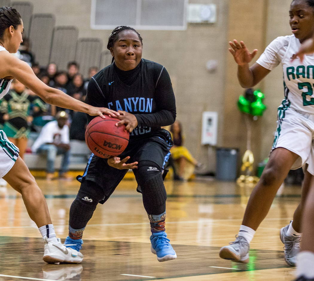 Canyon Springs' Ke'Ajanae Haley (13) attempts to get around Rancho defenders Kyndal Ricks (24), right, and Lea Williams (1) at Rancho High School in Las Vegas on Tuesday, Feb. 6, 2018. Canyon Spri ...