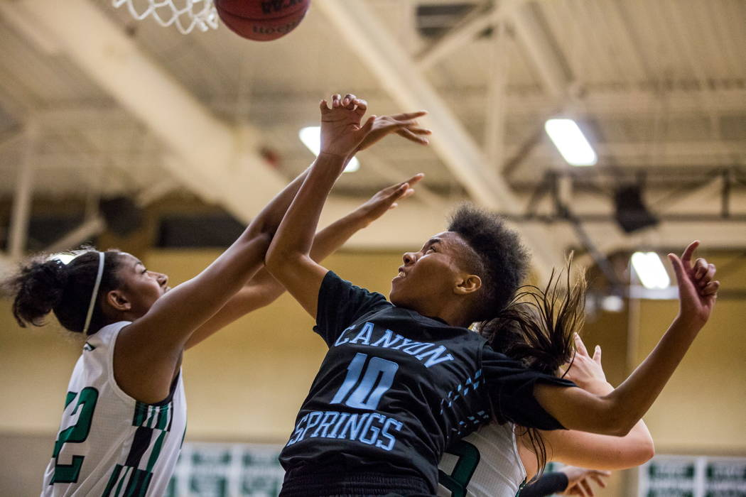 Canyon Springs' Kayla Johnson (10) reaches for the ball while competing with Rancho's Taylor DeGourville (42), left, and Kekai States (3) at Rancho High School in Las Vegas on Tuesday, Feb. 6, 201 ...