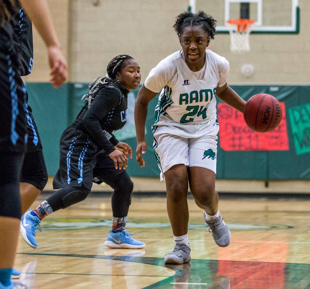 Rancho's Kyndal Ricks (24) takes the ball down the court while Canyon Springs' Ke'Ajanae Haley (13) comes up behind her at Rancho High School in Las Vegas on Tuesday, Feb. 6, 2018. Canyon Springs  ...