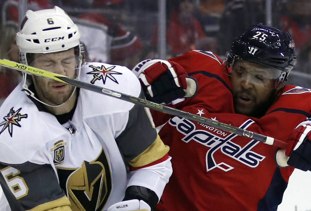 Vegas Golden Knights defenseman Colin Miller (6) takes a stick to the nose from Washington Capitals right wing Devante Smith-Pelly (25) in the second period of an NHL hockey game, Sunday, Feb. 4,  ...
