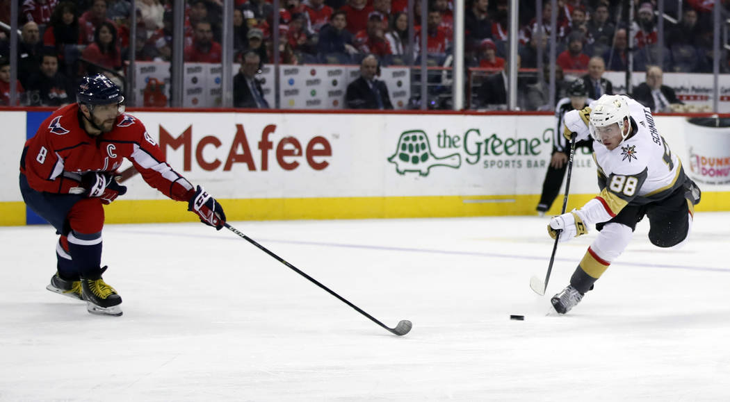 Vegas Golden Knights defenseman Nate Schmidt (88) shoots past Washington Capitals left wing Alex Ovechkin (8), from Russia, in the first period of an NHL hockey game, Sunday, Feb. 4, 2018, in Wash ...