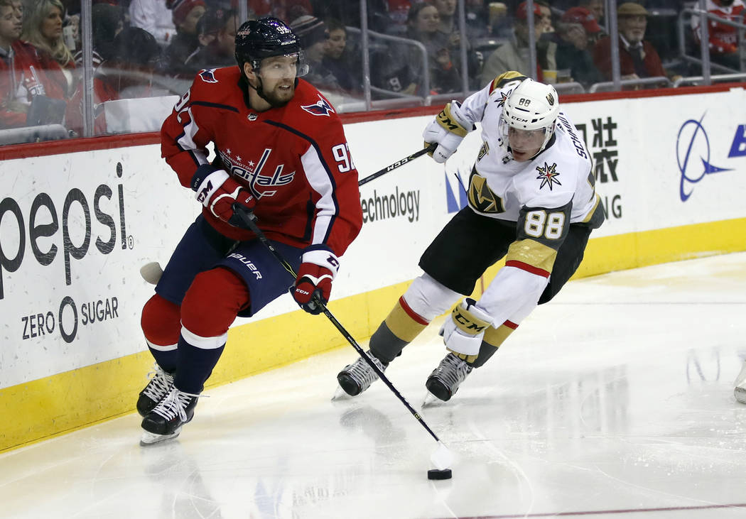 Washington Capitals center Evgeny Kuznetsov (92), from Russia, looks to pass as Vegas Golden Knights defenseman Nate Schmidt (88) defends in the second period of an NHL hockey game, Sunday, Feb. 4 ...