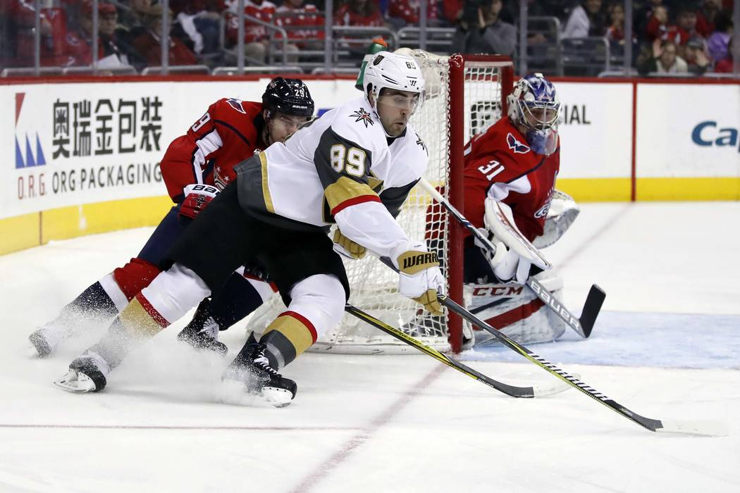 Vegas Golden Knights right wing Alex Tuch (89) skates with the puck as Washington Capitals defenseman Christian Djoos (29), from Sweden, and goaltender Philipp Grubauer (31), watch during the firs ...