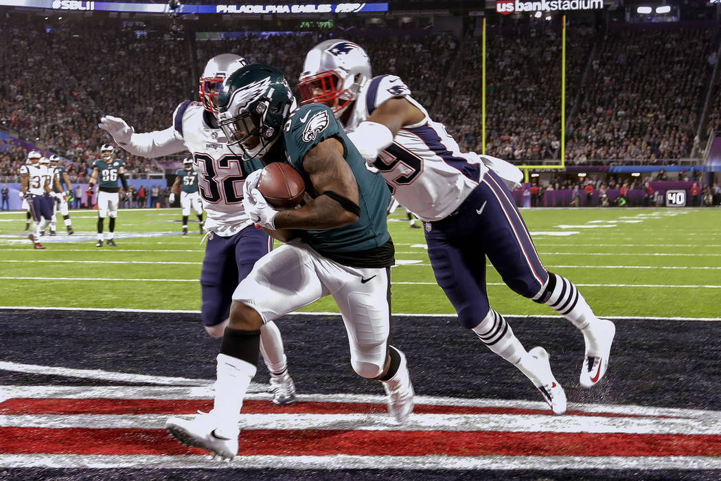 Philadelphia Eagles running back Corey Clement (30) scores a touchdown, as New England Patriots cornerback Johnson Bademosi (29) and free safety Devin McCourty (32) are late with the tackle, durin ...