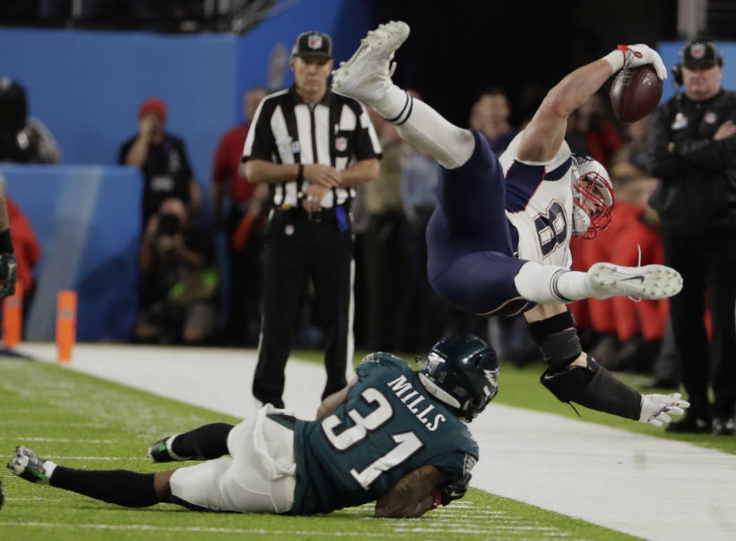 Philadelphia Eagles cornerback Jalen Mills (31) tackles New England Patriots tight end Rob Gronkowski (87), during the second half of the NFL Super Bowl 52 football game, Sunday, Feb. 4, 2018, in  ...