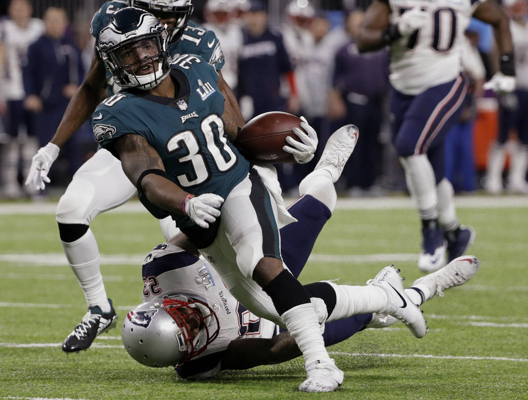 Philadelphia Eagles running back Corey Clement (30) is tackled by New England Patriots strong safety Patrick Chung (23), during the first half of the NFL Super Bowl 52 football game, Sunday, Feb.  ...