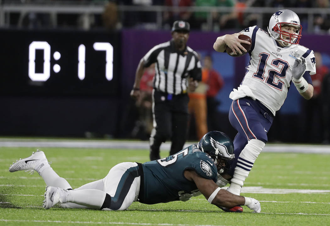 New England Patriots' Tom Brady (12) runs from Philadelphia Eagles' Brandon Graham during the first half of the NFL Super Bowl 52 football game Sunday, Feb. 4, 2018, in Minneapolis. (AP Photo/Mark ...