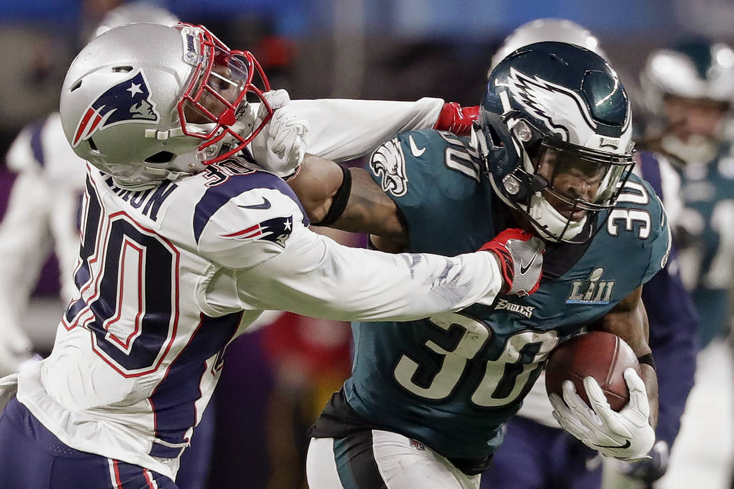 Philadelphia Eagles running back Corey Clement (30), right, runs against New England Patriots strong safety Duron Harmon (30), during the first half of the NFL Super Bowl 52 football game, Sunday, ...
