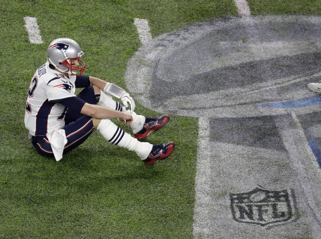 New England Patriots quarterback Tom Brady sits on the field after fumbling against the Philadelphia Eagles during the second half of the NFL Super Bowl 52 football game Sunday, Feb. 4, 2018, in M ...