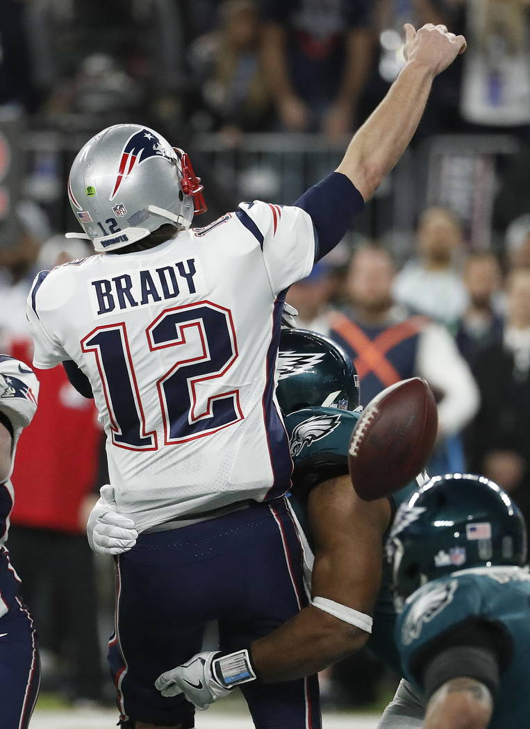 Philadelphia Eagles' Brandon Graham, center, strips the ball from New England Patriots quarterback Tom Brady during the second half of the NFL Super Bowl 52 football game Sunday, Feb. 4, 2018, in  ...