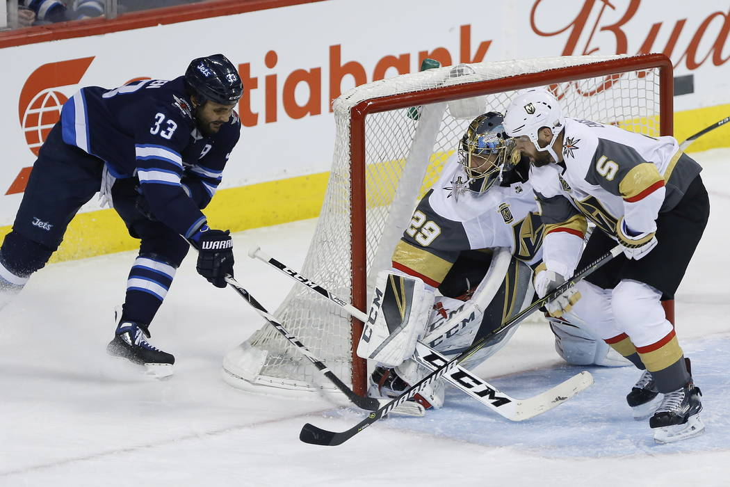 Winnipeg Jets' Dustin Byfuglien (33) attempts the wraparound on Vegas Golden Knights goaltender Marc-Andre Fleury (29) and Deryk Engelland (5) during the first period of an NHL hockey game Thursda ...