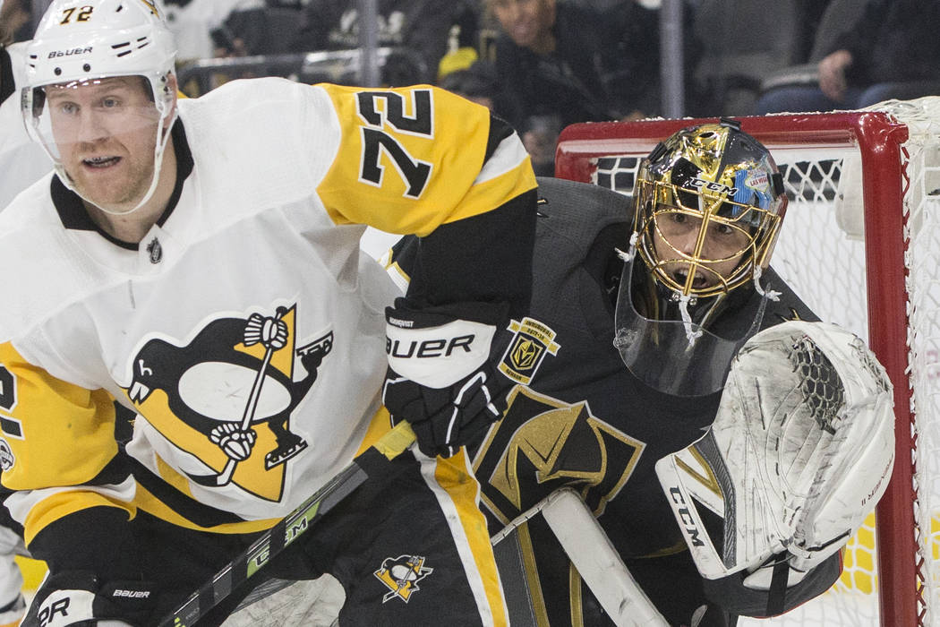 Golden Knights goaltender Marc-Andre Fleury (29) fights for position with Penguins right wing Patric Hornqvist (72) during the second period of Vegas' home matchup with Pittsburgh on Thursday, Dec ...