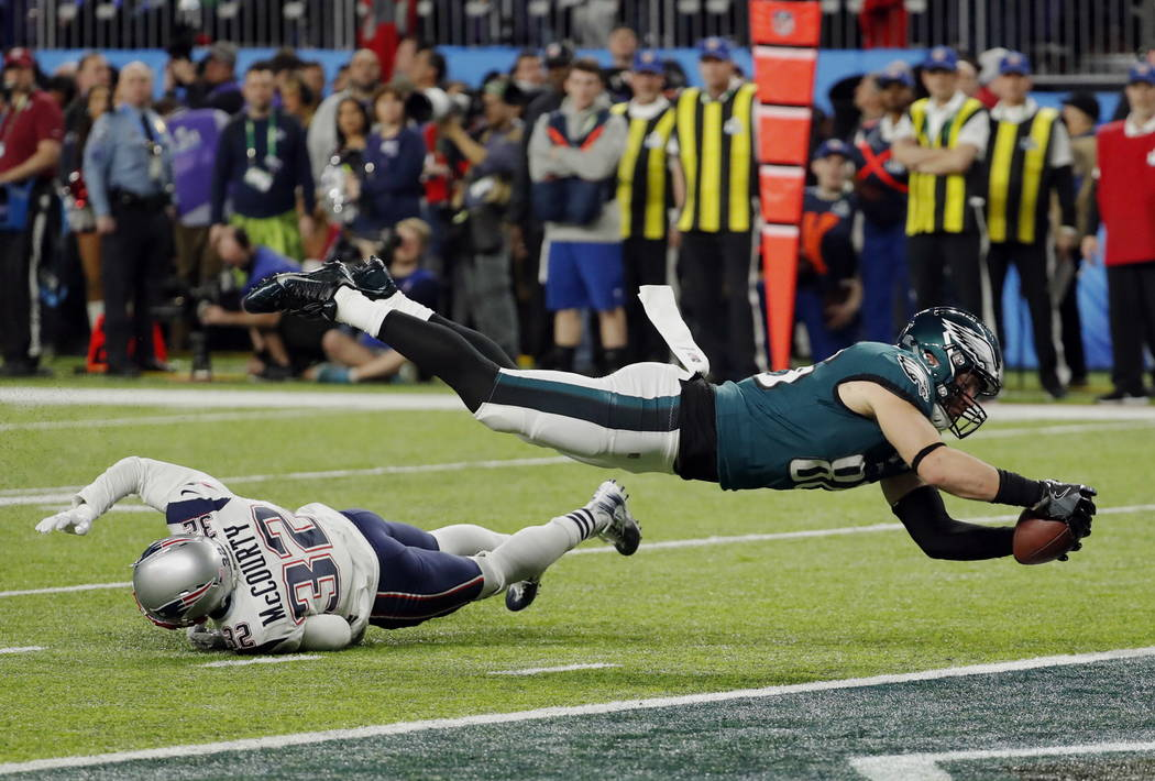 Philadelphia Eagles tight end Zach Ertz (86) dives into the end zone over New England Patriots free safety Devin McCourty (32) for a touchdown, during the second half of the NFL Super Bowl 52 foot ...