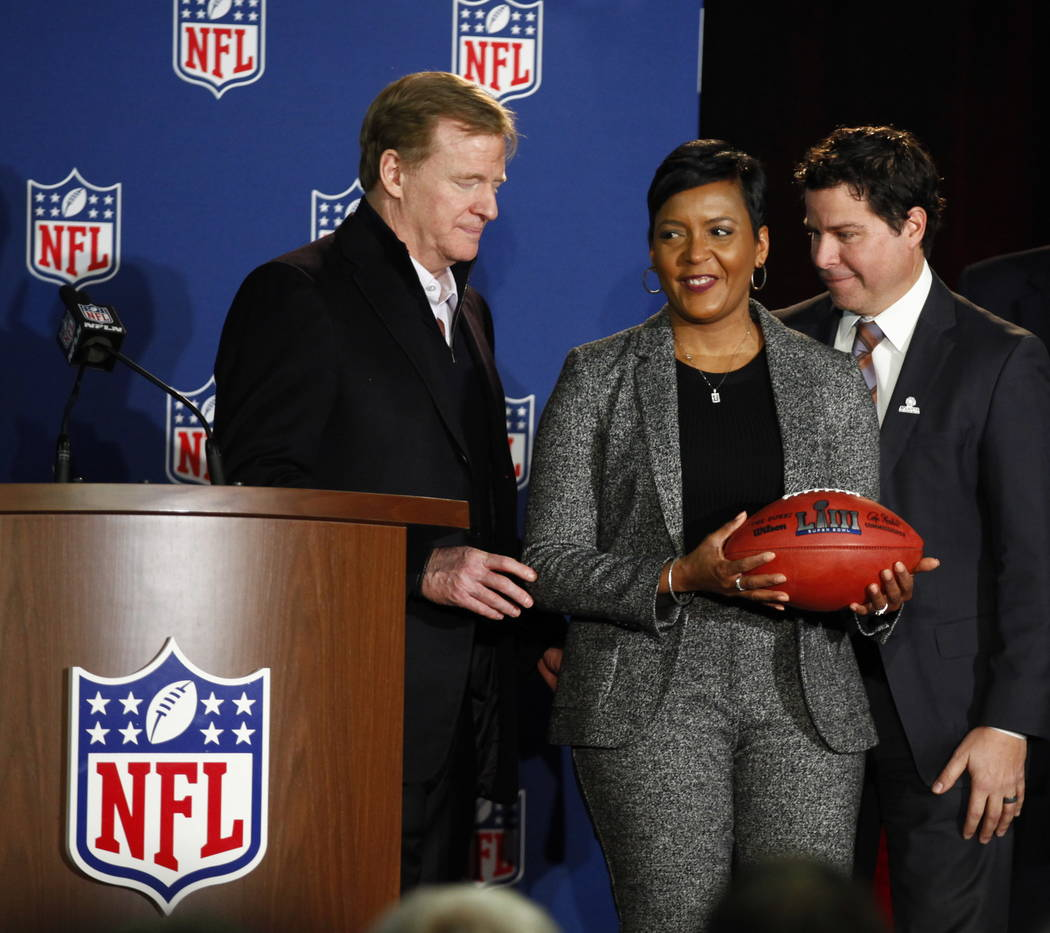 NFL Commissioner Roger Goodell, left, signifies the changing of Super Bowl host cities by handing the Mayor of Atlanta, Keisha Lance Bottoms, center, a Super Bowl LIII football as Atlanta Sports C ...